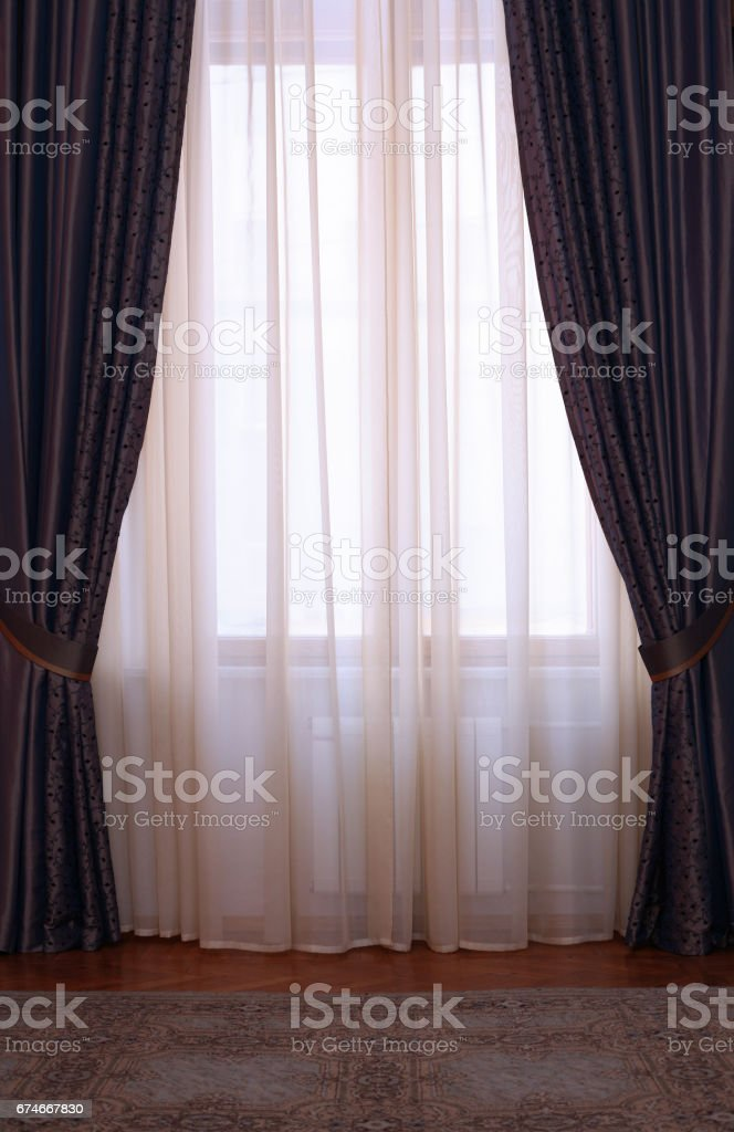 Two identical portieres between which window stock photo