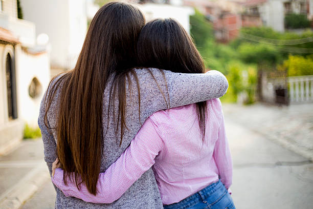 Two identical teenage girlfriends, shot from back Two identical teenage girlfriends, shot from back sister stock pictures, royalty-free photos & images