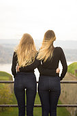 Two identical teenage girlfriends, shot from back. Rear view