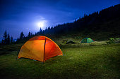 istock Two Illuminated orange and green camping tents 580116712