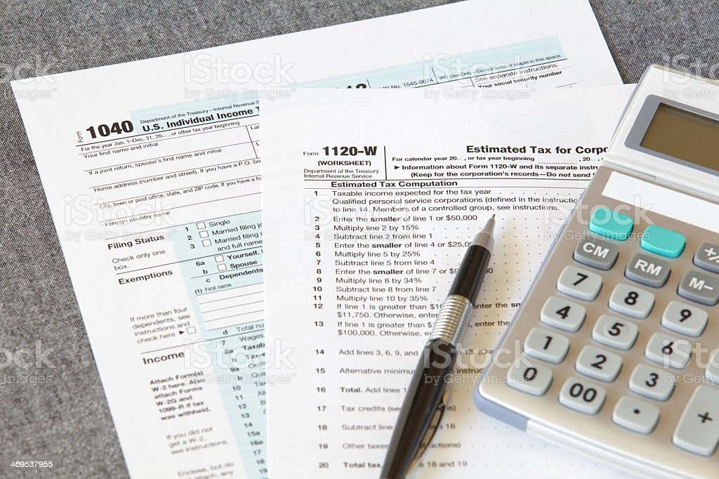 Two income tax forms with pen and calculator stock photo