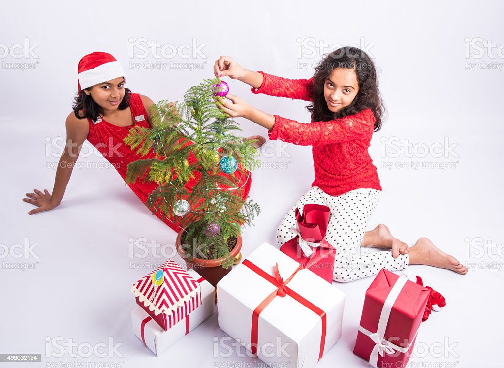 Two Indian Girls Decorating Christmas Tree With Gifts Stock
