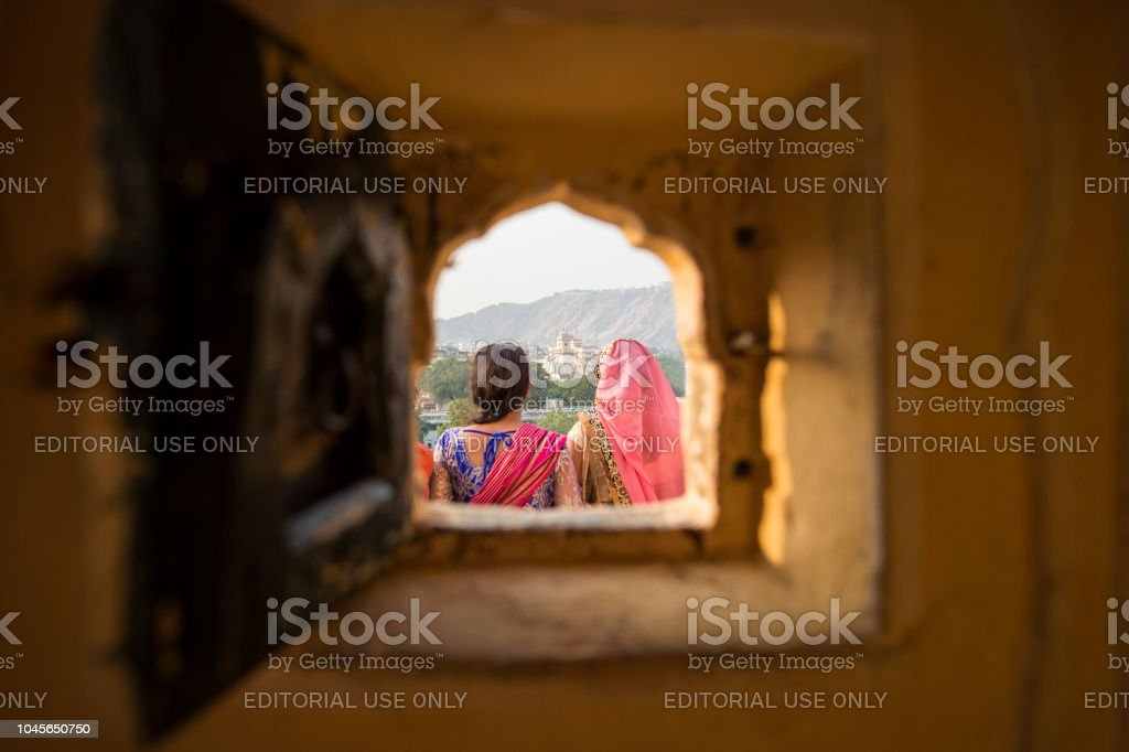 Two Indian girls wearing the traditional Indian dress 'Sari' are admiring the landscape of Jaipur. Photo taken from a small window on the Hawa Mahal in Jaipur, India. stock photo