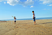 istock Two Indian kids in matching t shirts playing cricket on a beach by the sea on a bright sunny summer day. 1137358950