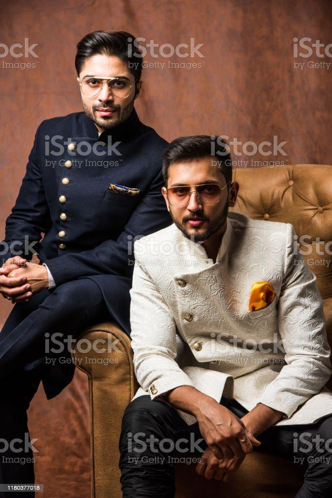 Two Indian Male Models Posing With Ethnic Wear Like Sherwani Jodhpuri Or Kurta Pyjama While Sitting On Wing Chair Stock Photo Download Image Now Istock