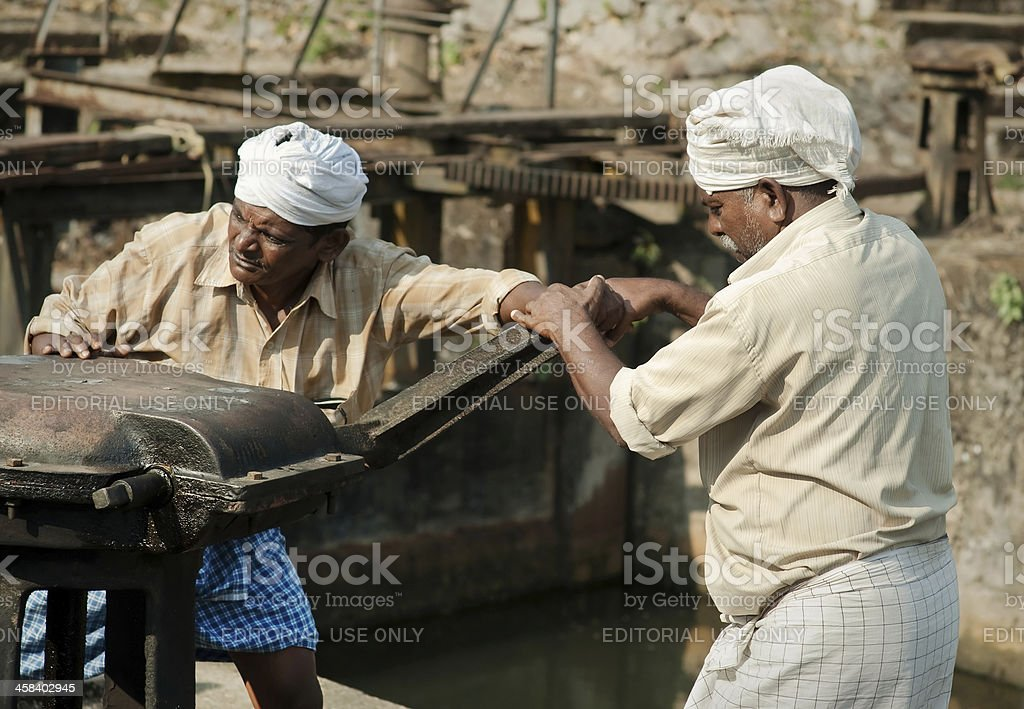 Two indian men opening sluice gates. stock photo