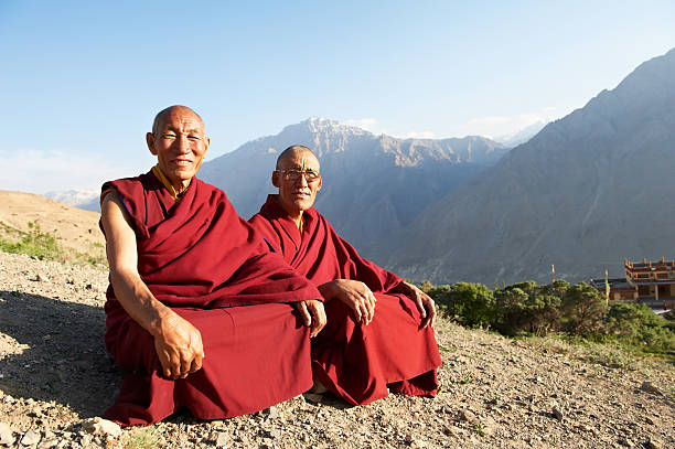 Two Indian Tibetan monks are sitting on a mountain stock photo