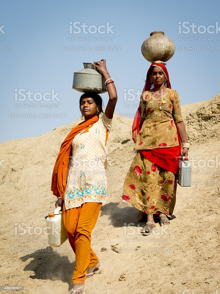 Two Indian women carrying water. stock photo