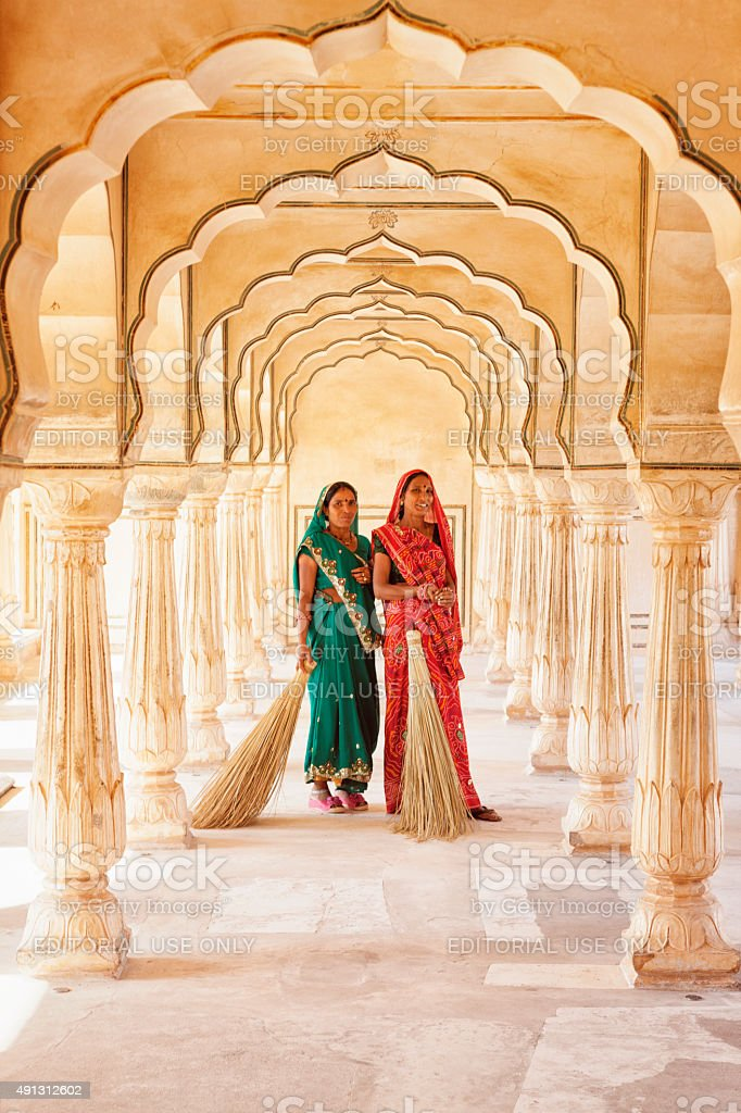 Two Indian women standing under the Amer Fort architecture stock photo
