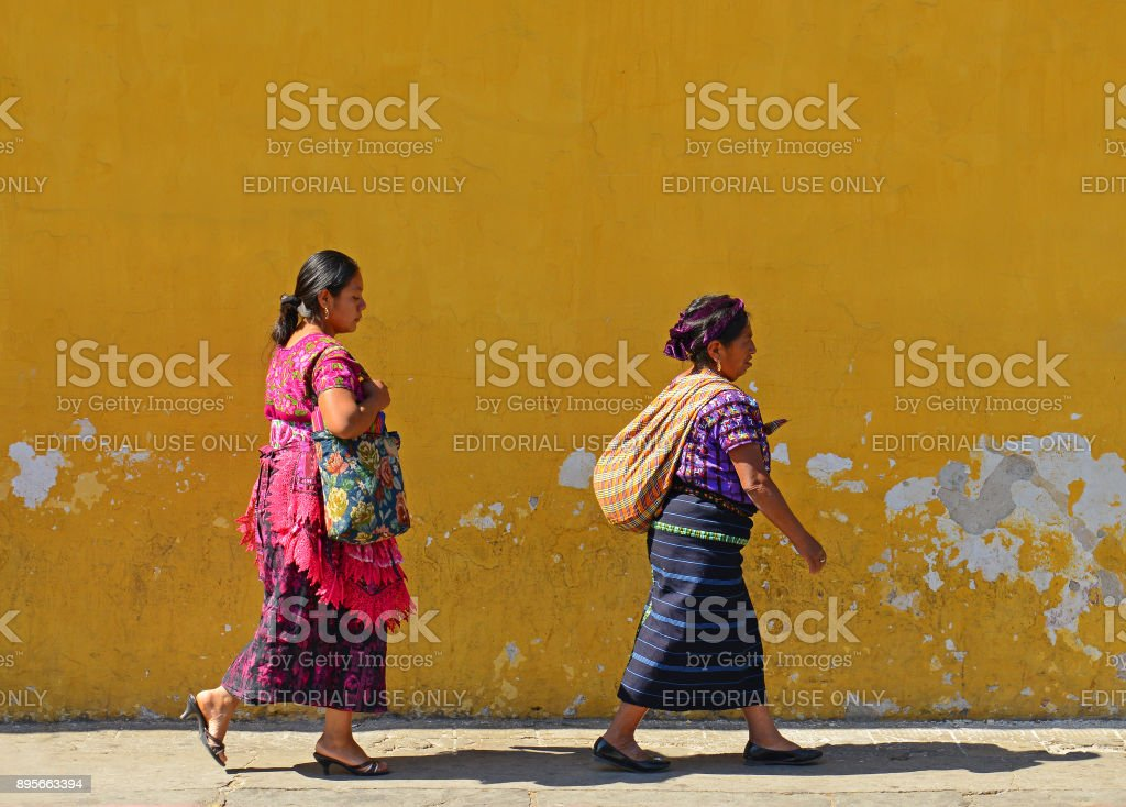 Two indigenous Mayan women walking in traditional clothing in front...