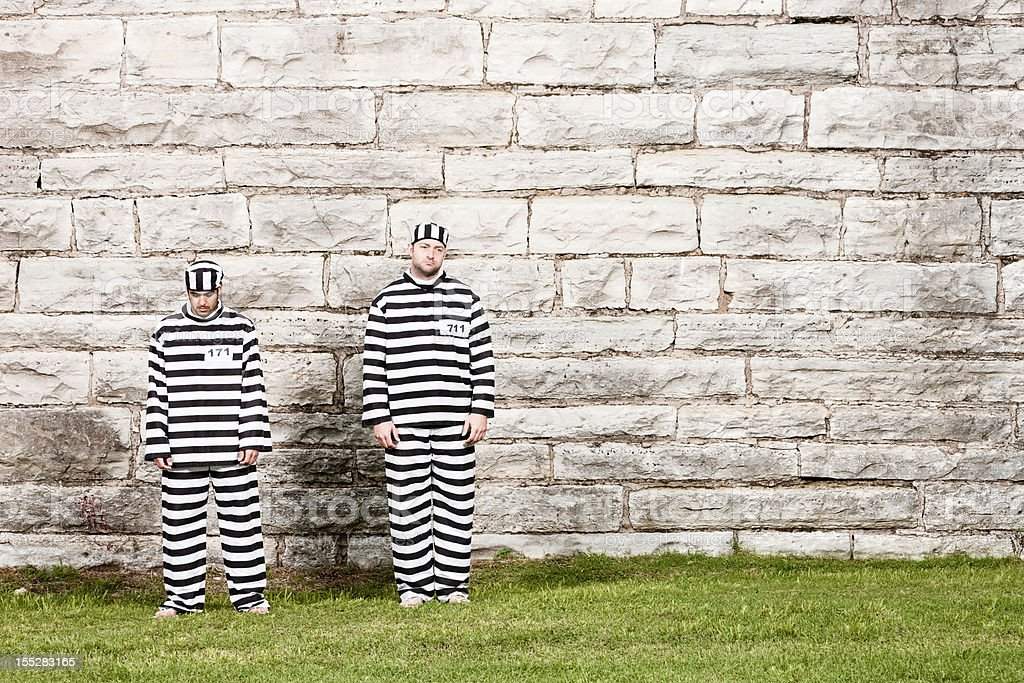 Two Inmates Stand in Front of Prison Wall stock photo