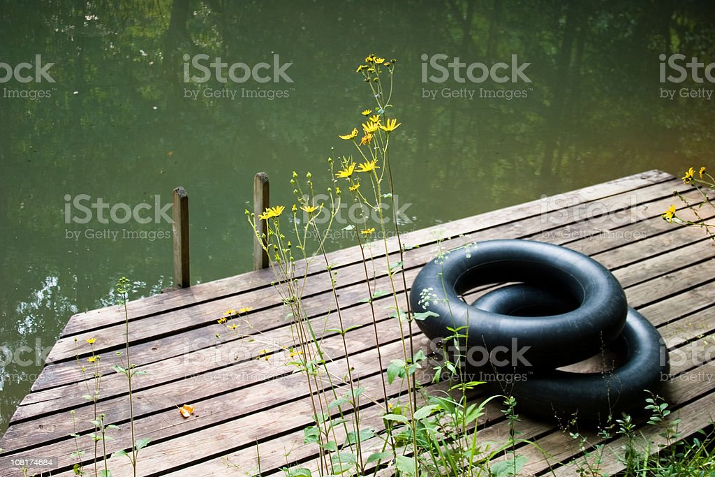 Two Inner Tubes Sitting on Lake Dock stock photo