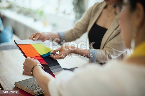 two interior designers discussing fabric sample in the studio stock
