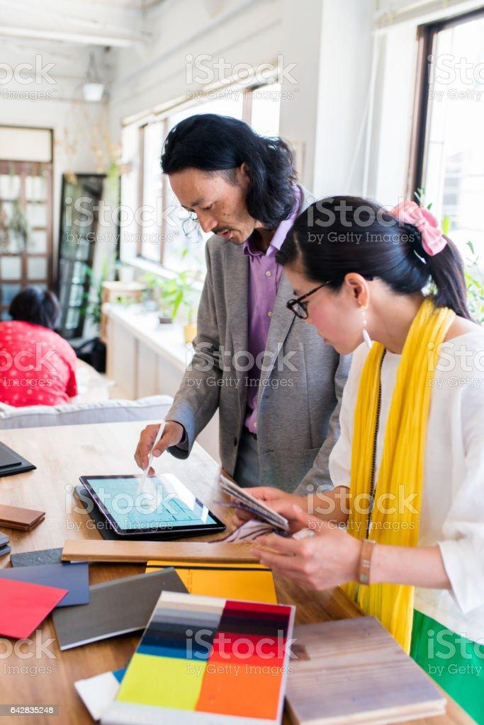 two interior designers discussing sample materials stock photo