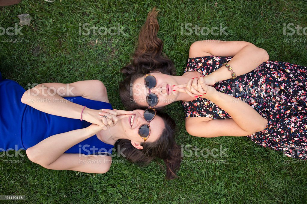 Two intimate cute girls, relaxing in grass. Hand 'gun' stock photo