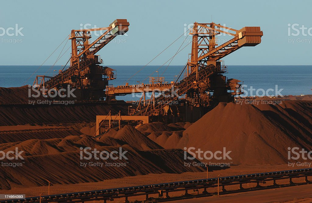 Two iron ore stackers working in a stockyard. royalty-free stock photo