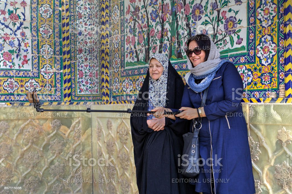 Two islamic women make selfie in courtyard of the mosque. stock photo