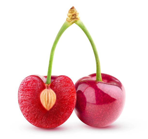 Two isolated cherries, one cut in half stock photo