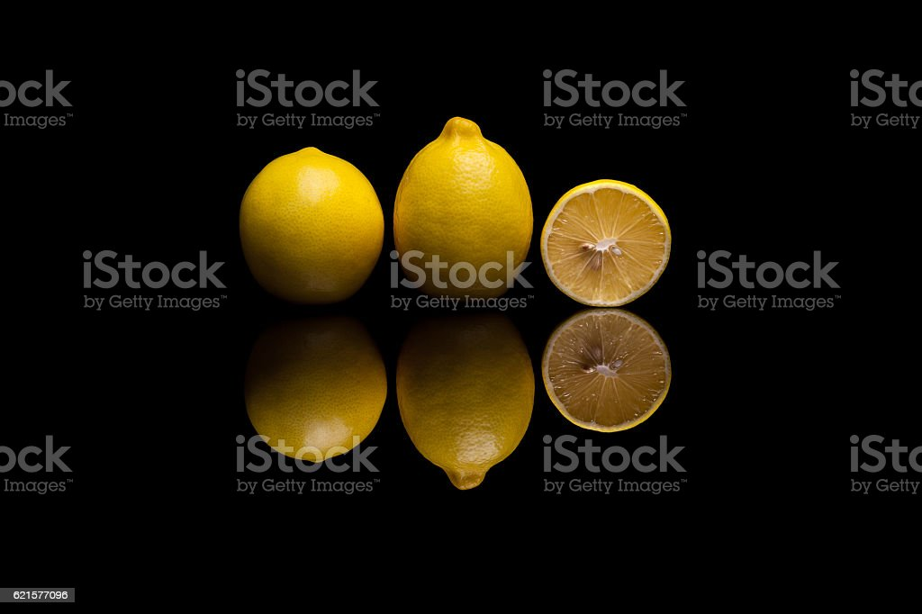 Two isolated yellow lemons and one halved on black background photo libre de droits