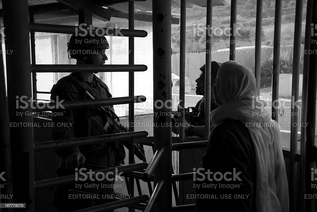 Two Israeli soliders and Palestinian woman at West Bank checkpoint royalty-free stock photo