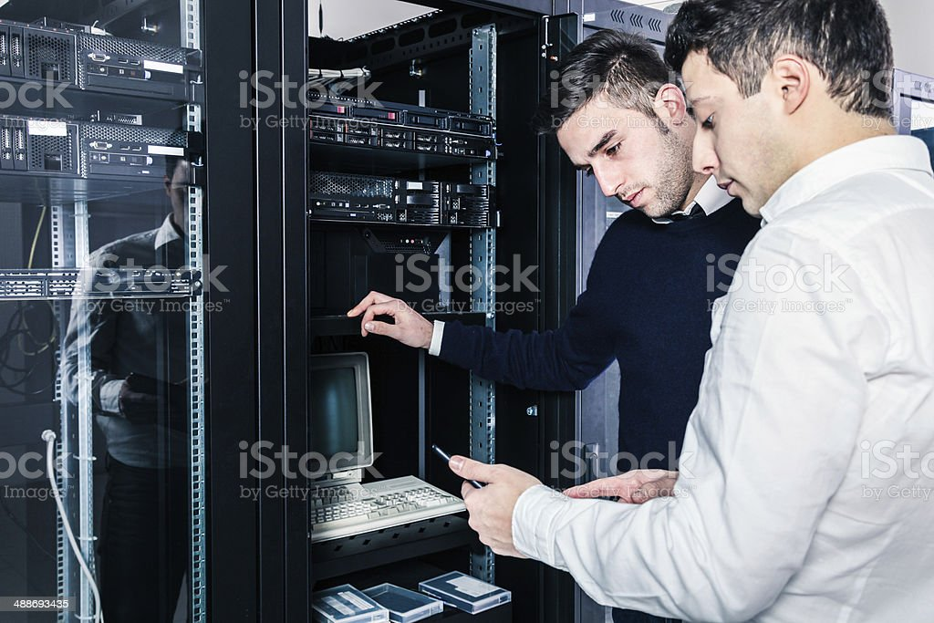 Two IT engineering working on a server stock photo