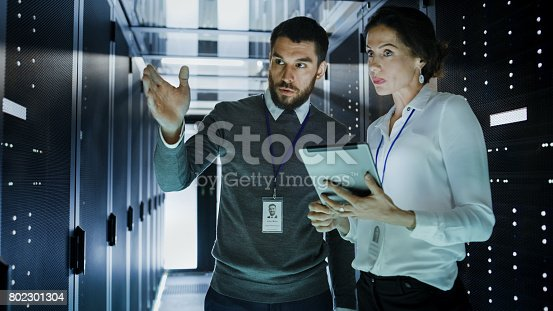 istock Two IT Engineers in Data Center / Server Room, Talking, one of them Pointing Forward, Other Holds Tablet Computer. 802301304