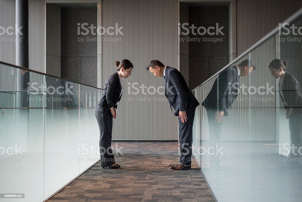 Two Japanese business people bowing towards each other stock photo