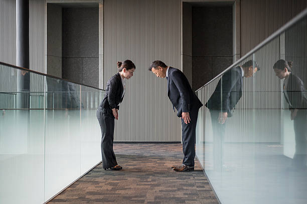 two japanese business people bowing towards each other - お礼 ストックフォトと画像
