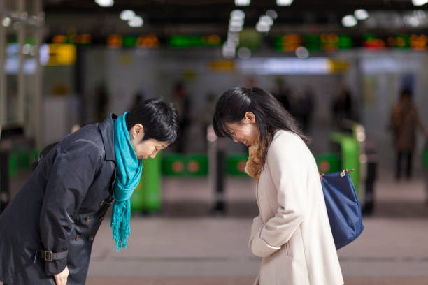 Two Japanese Businesswomen Bowing To Each Other At Station stock photo