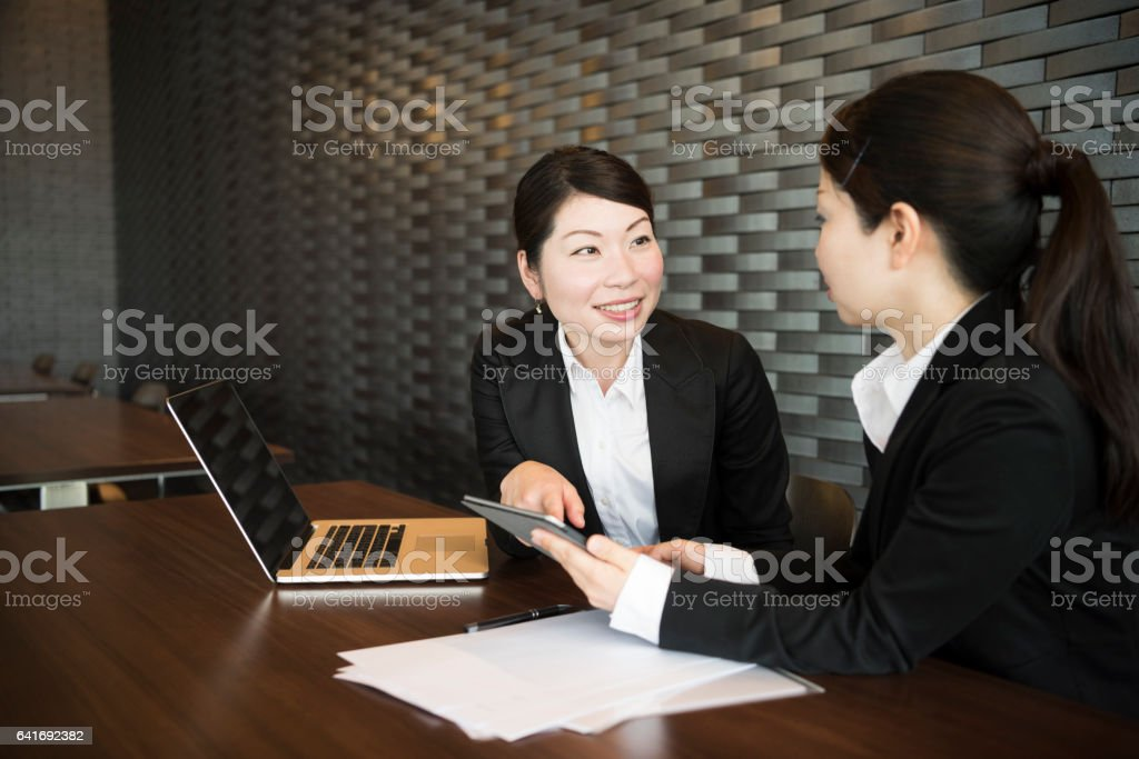 Two Japanese businesswomen sitting at desk with laptop, talking stock photo