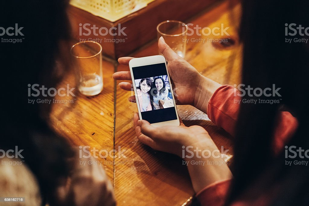 Two japanese female friends at restaurant taking seflie stock photo