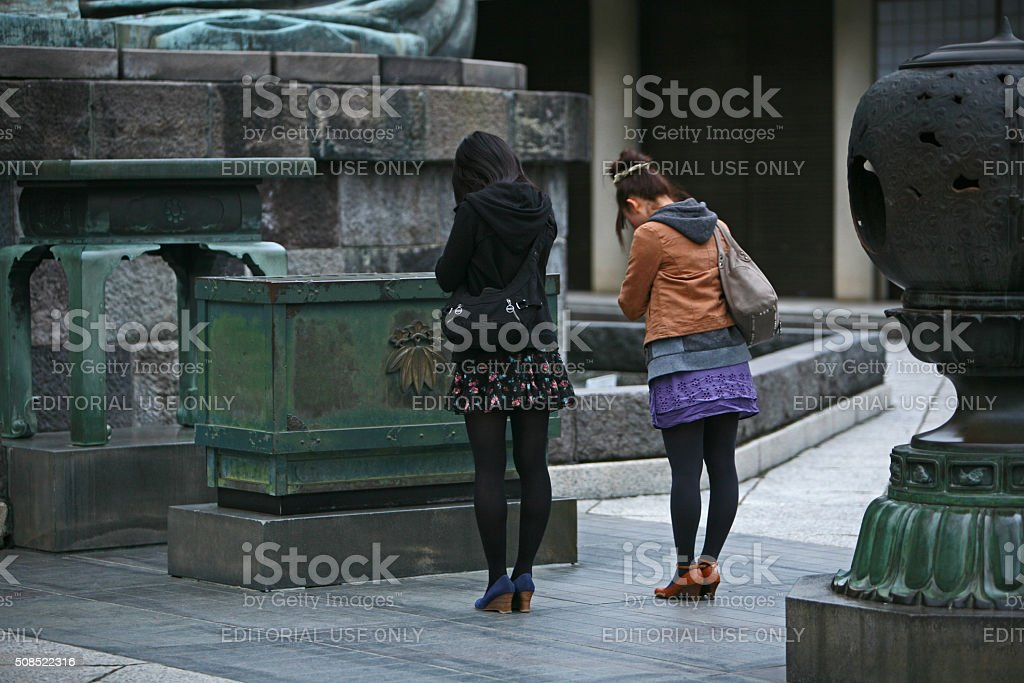 Two Japanese girls before the statue of Great Buddha. stock photo