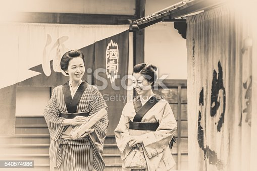 Vintage styled image composition of Japanese women dressed traditionally in Kimono and talking a stroll around their village.