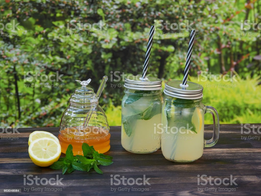 Two jars of fresh lemonade with mineral water, mint, and honey stock photo