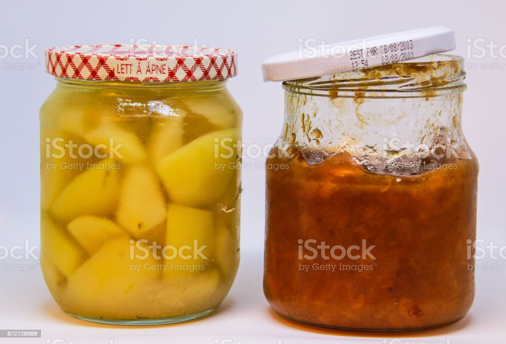 Two jars with home made canned pears and plum jam stock photo