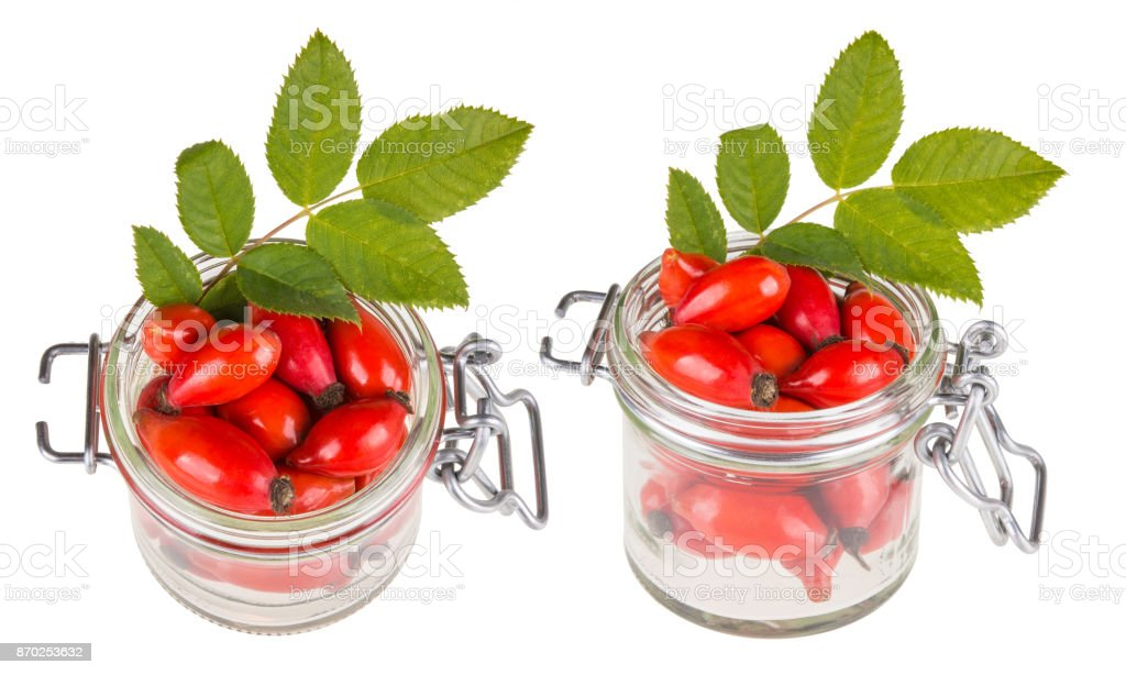 Two jars with red rosehips and green leaves stock photo