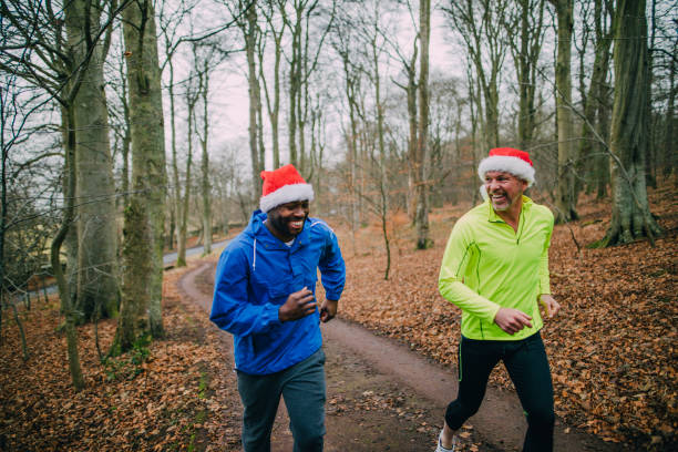 two joggers up the trails in the forest at christmas - santa hat stock pictures, royalty-free photos & images