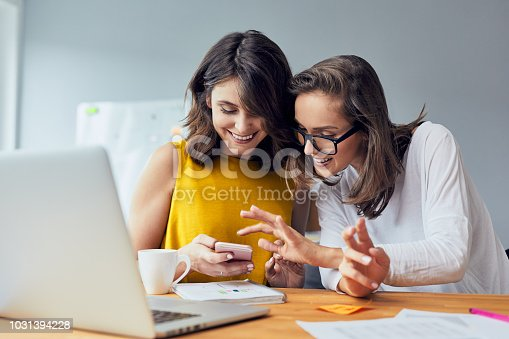 1031394390 istock photo Two joyful coworkers browsing phone laughing together while taking break from work in the office 1031394228