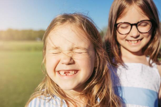 sarılma ve güneş onların gözlerinden kapalı iki joyfull kız. - doğal poz stok fotoğraflar ve resimler