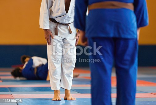 istock Two judo fighters or athletes greeting each other in a bow before practicing martial arts 1153199728
