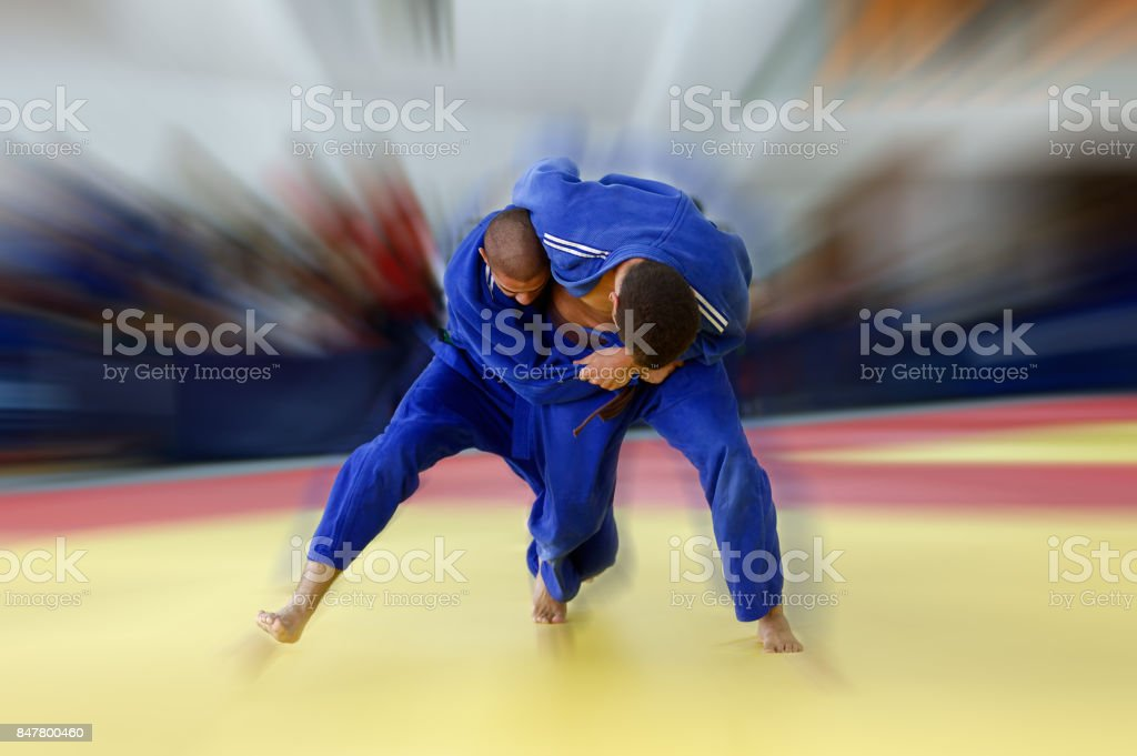 Two judokas in blue judogis fighting stock photo