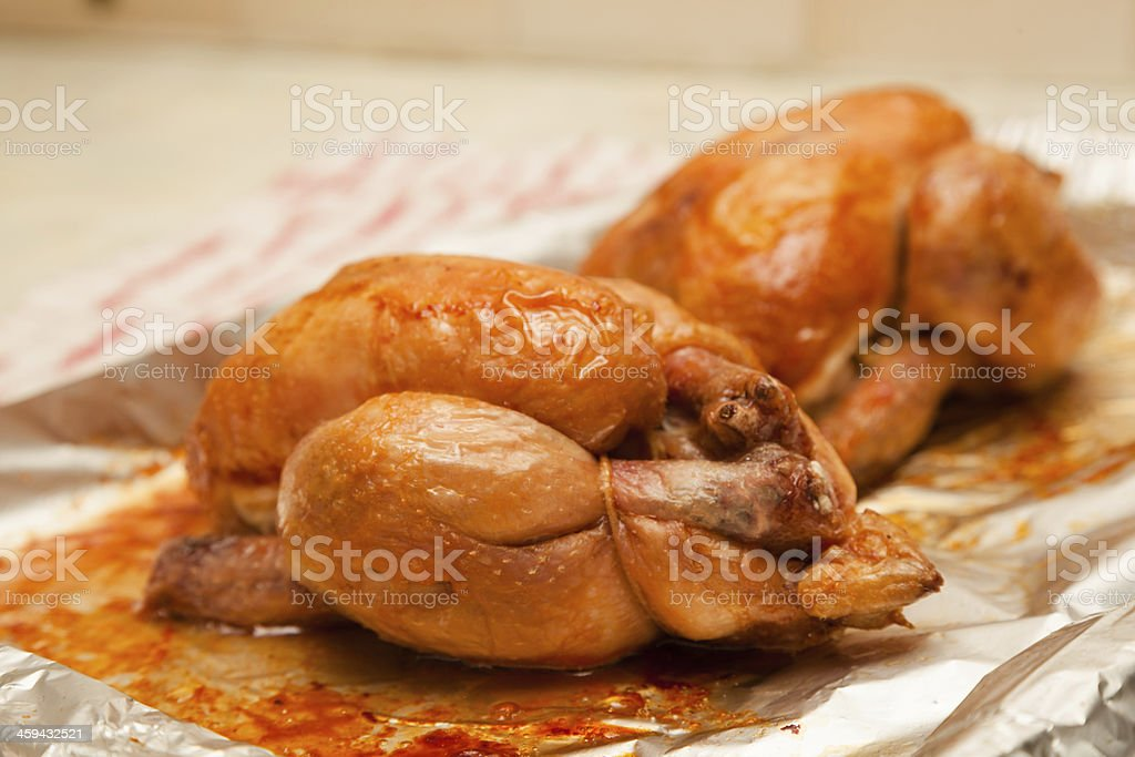 two juicy roasted poussin on aluminium foil from oven stock photo