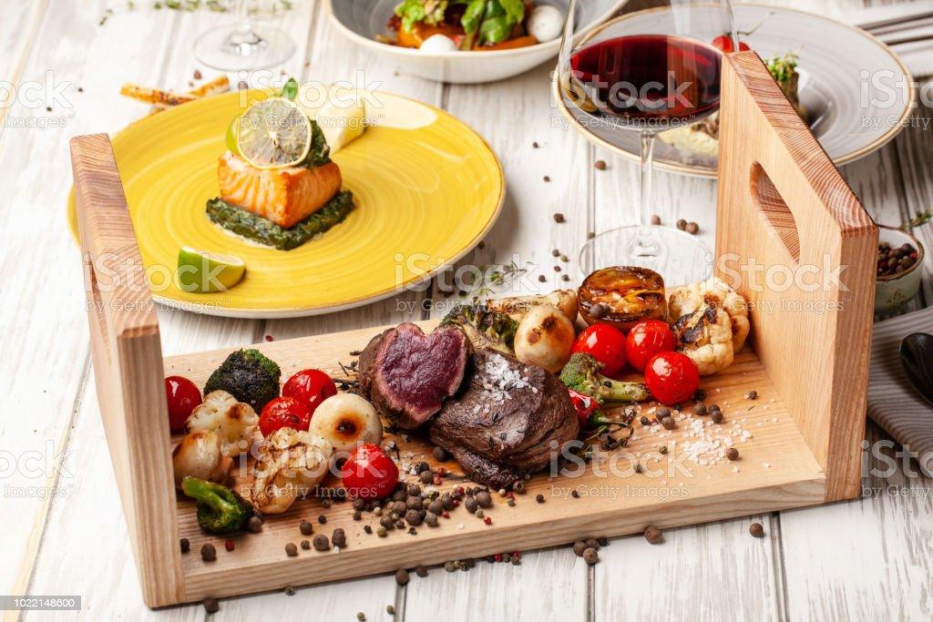 Dois bifes suculentos com assado lombo, com legumes grelhados em uma placa de madeira. Cozido com fritadeiras de ar. Uma tabela descontraída no restaurante para um feriado ou aniversário, noite de jantar. foco seletivo - foto de acervo