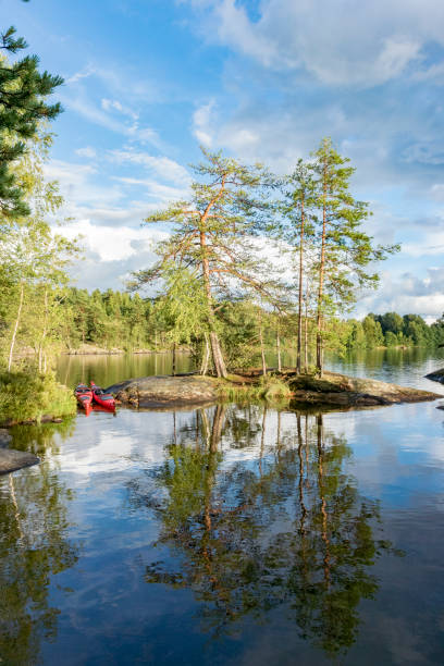 Two kayaks on the shore of a calm lake in Sweden during a kayaking trip. stock photo