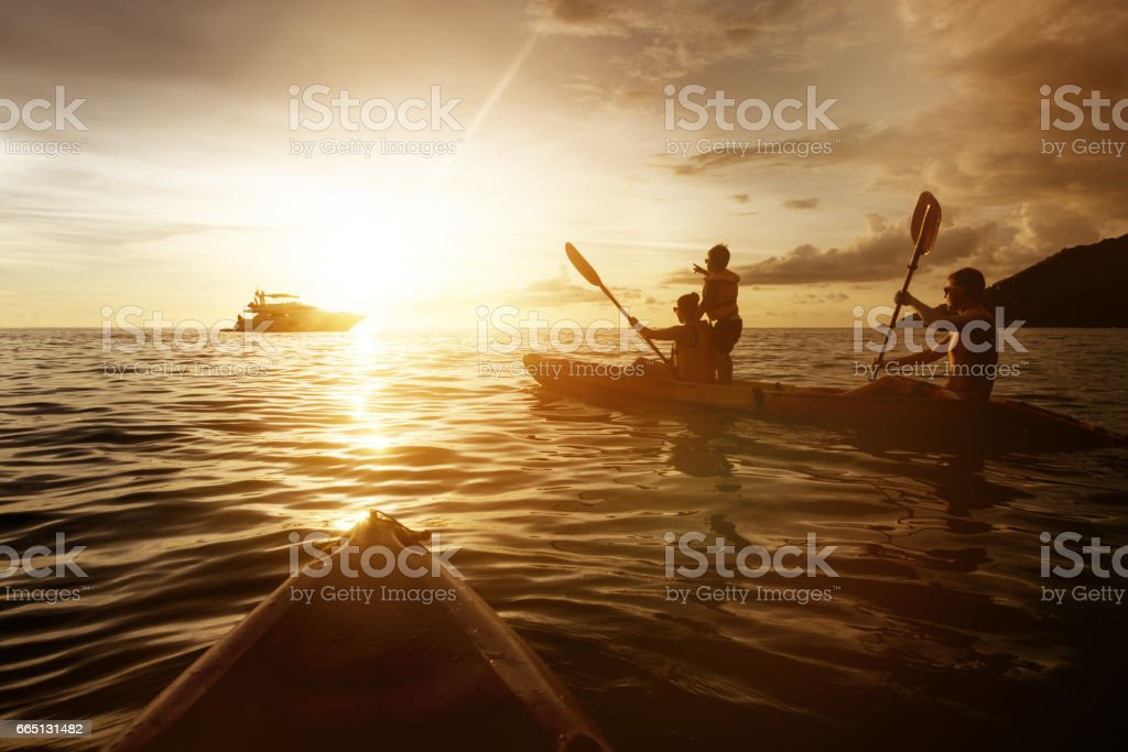 Two kayaks with family at sunset sea stock photo