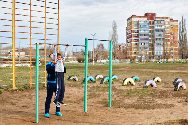 two kazakh brothers play outdoor sports - horizontal bar stock photos and pictures