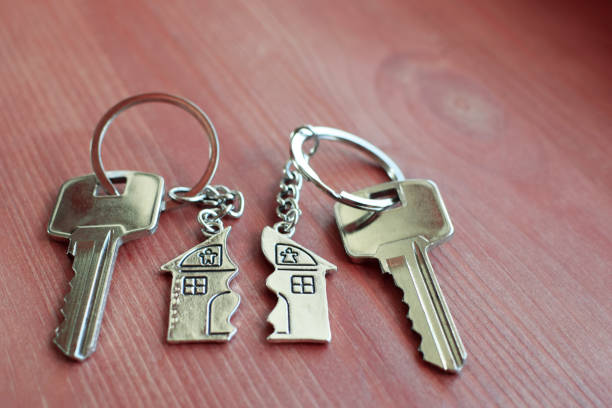 two keys with splitted key rings with pendant in shape of house - divorzio foto e immagini stock