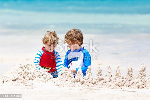 Two little kids boys having fun with building a sand castle on tropical beach of Playa del Carmen, Mexico. children playing together on their vacations Twins, Happy brothers laughing and smiling
