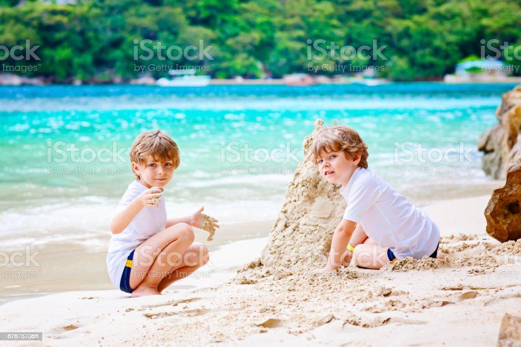 Deux enfants garçon château de sable sur la plage tropicale photo libre de droits