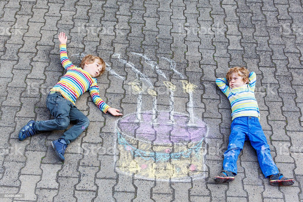 Two kid boys having fun with colorful birthday cake chalks stock photo
